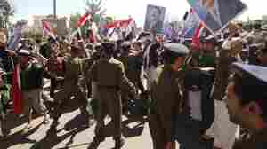 Yemeni security forces stand between pro-regime supporters (right) and  anti-government protesters (unseen in picture) during demonstrations  outside Sanaa University in the Yemeni capital on Tuesday.