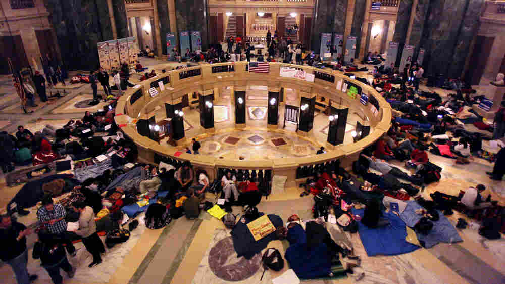 People in sleeping bags hold a vigil at the state Capitol as testimony at a hearing on the budget continues into the wee hours on Wednesday.
