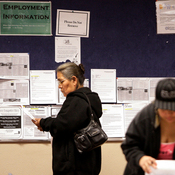 Job seekers read their resumes as they stand near a bulletin board with job posting fliers on it at the Arizona Workforce Connection West Valley Career Center in Phoenix. Foreign-born workers have had better employment prospects than U.S. natives.