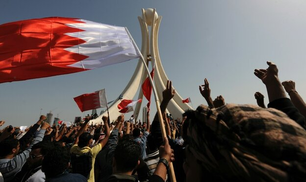 Bahraini protesters wave the national flag and chant slogans as they gather Wednesday at Pearl Square in the capital city of Manama.
