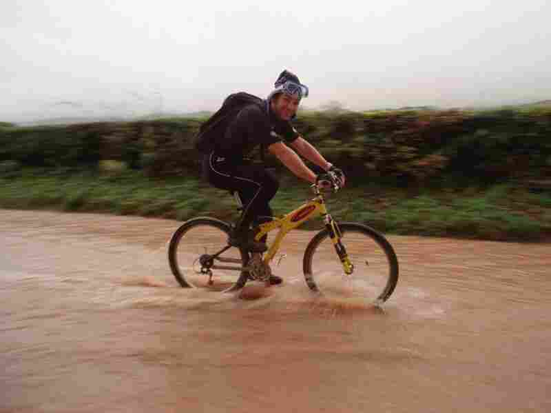 A cyclist wearing a wet suit cycles to work on Nov. 7, 2000, as roads in North Wales were impassable by vehicles. Computer models of the climate show that heavy rains were less likely to occur in a simulated world without global warming.