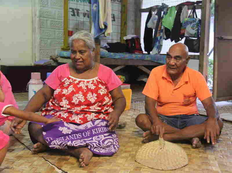 Batie Tebwa and Baure Karakaua sit on the floor of their home in Kiribati. Their daughter, Tiibea Baure, has repeatedly tried to convince them that climate  change is a threat, but they don't believe in it.