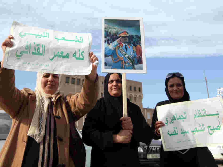 Libyan pro-government supporters hold a portrait of leader Moammar Gadhafi during a rally Wednesday in Tripoli.
