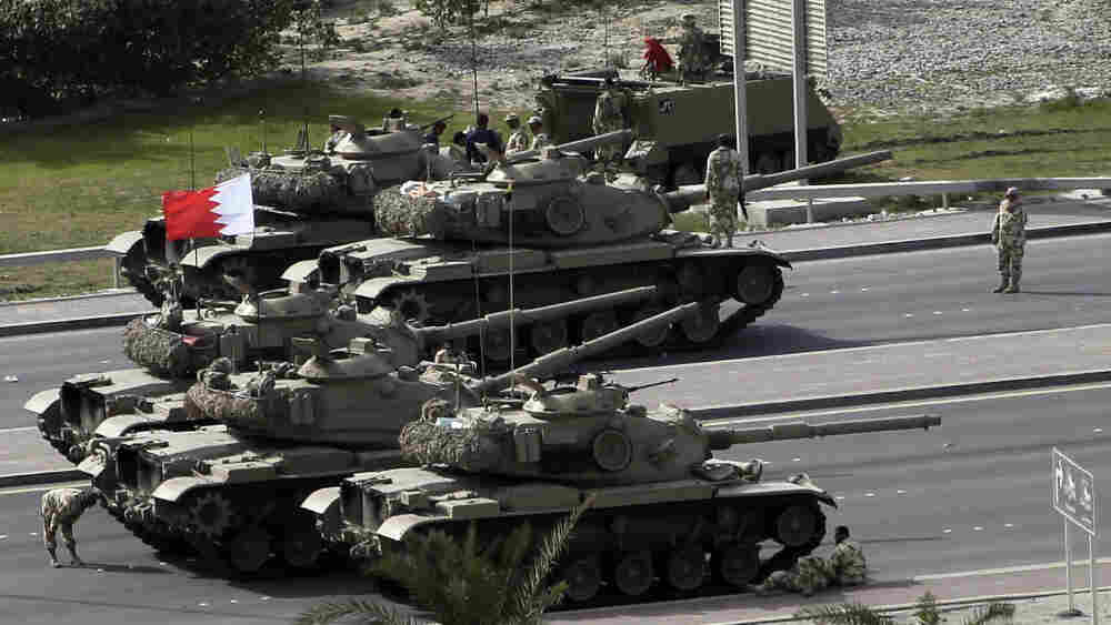 Bahraini army tanks take position near Pearl Square in Manama on Thursday after anti-riot police stormed through the square.