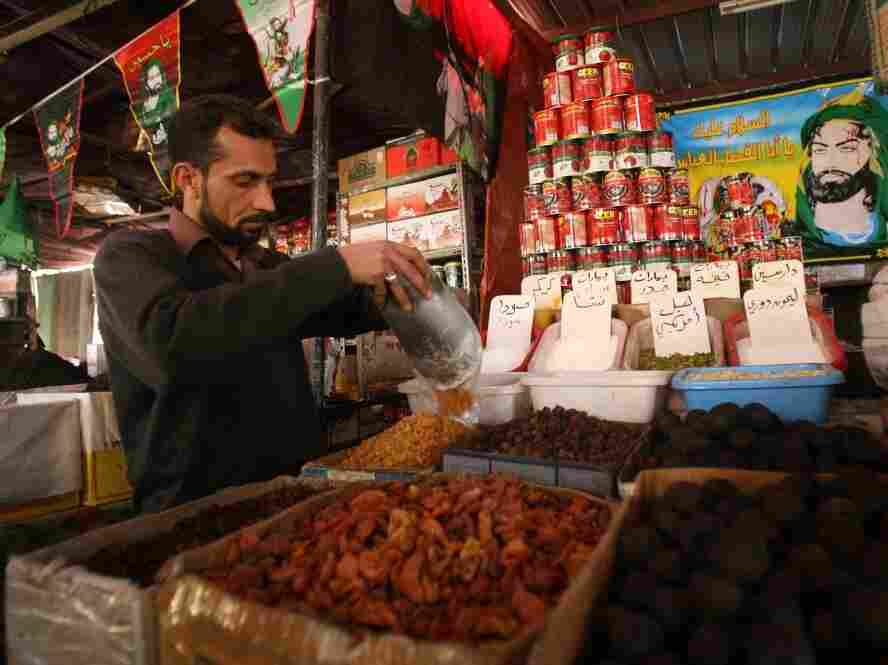 """An Iraqi shop owner sells groceries in Baghdad. World Bank President Robert Zoellick says the high cost of food is an """"aggravating factor"""" behind the unrest in the Middle East."""