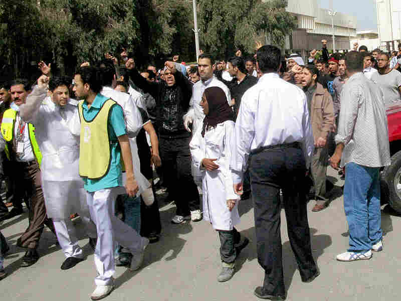 Nurses and medical workers march in protest, demanding the resignation of the health minister, after ambulances were blocked from reaching the wounded during Thursday's violent crackdown in Pearl  Square.