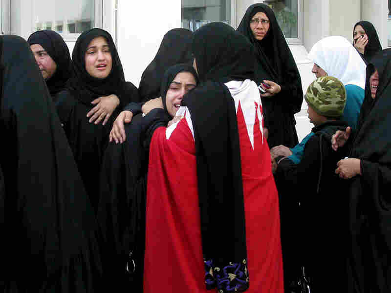 Women in Manama, Bahrain, mourn over the dead and wounded from Thursday morning's police  raid of a protesters' camp in the capital's central square.