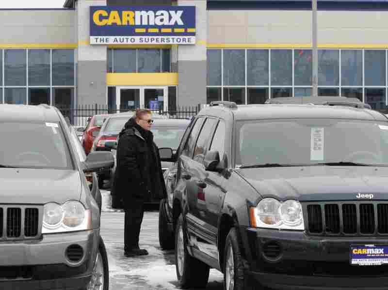 A potential customer walks past a row of cars for sale at the CarMax dealership in Oak Lawn, Ill.