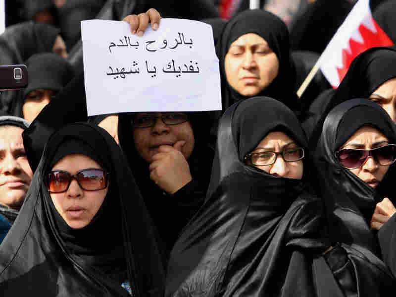 """A Bahraini Shiite woman holds a sign with the words """"We sacrifice our souls and blood for martyrs"""" written in Arabic during a funeral for men killed the day before during a violent police raid in Manama."""