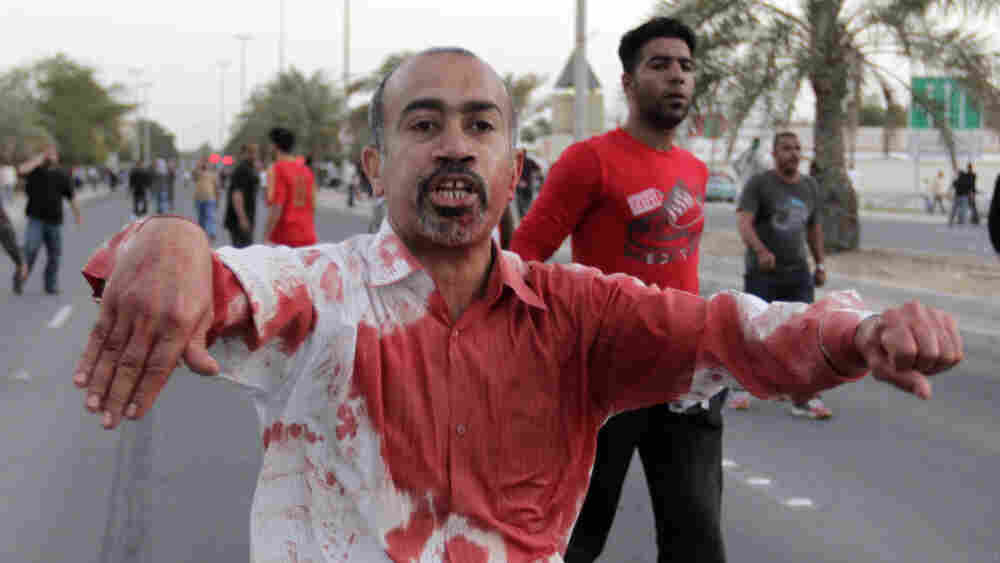 A Bahraini man is soaked in blood from helping an anti-government protester injured Friday in Manama. Troops attacked people who defied a government ban and streamed toward a downtown square that has been the symbolic center of the uprising.