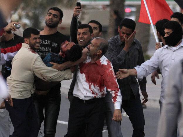 An unidentified man is carried to a vehicle to be taken to a hospital after being wounded during a demonstration in Manama, Bahrain, today (Feb. 18, 2011).