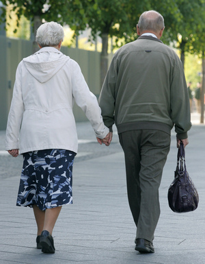 An elderly couple holds hands while walking along a Berlin street. A recent study showed that walking grows the region of the brain that archives memories.