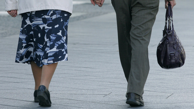 An elderly couple holds hands while walking along a Berlin street. A recent study showed that walking grows the region of the brain that archives memories. (AFP via Getty Images)