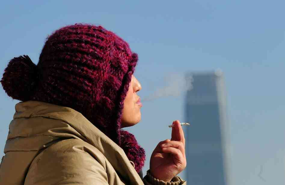 A woman smokes a cigarette in Beiijng.