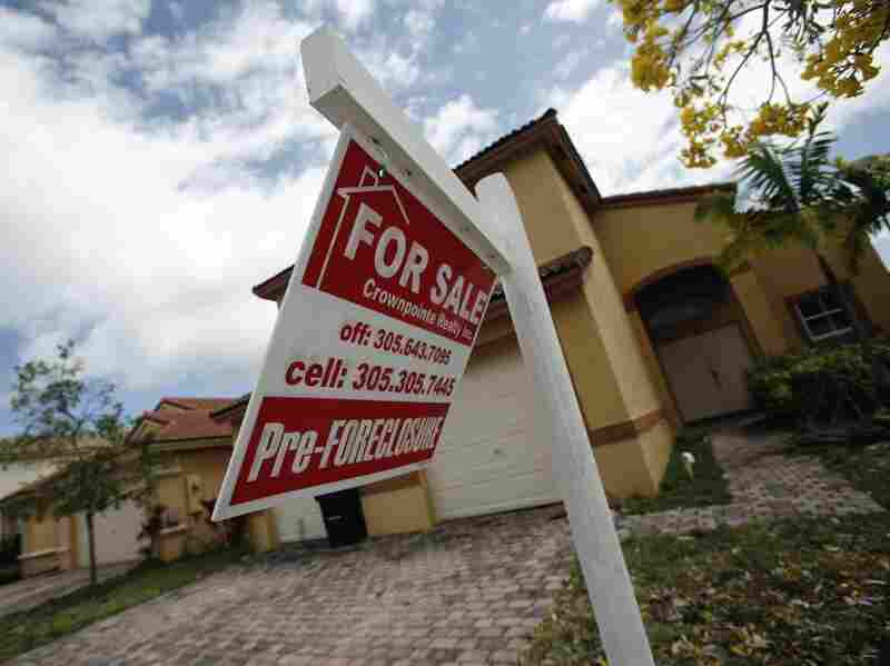 A for sale sign hangs in front of a Homestead, Fla., home. In certain places more than half of the homes sold are in one stage of foreclosure or another.