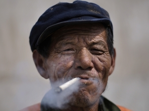An elderly Chinese construction worker smokes a cigarette while taking a break from work in Beijing.