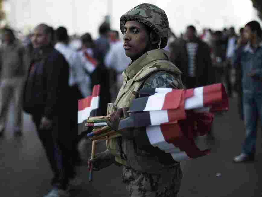 An Egyptian soldier greeted demonstrators with national flags today in Cairo's Tahrir Square.
