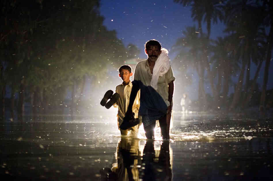 A Pakistani man and boy,  displaced by floods, walk through flood waters on Aug. 22, 2010 in the village of Baseera near Muzaffargarh in Punjab, Pakistan.