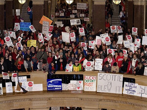 Protesters fill all three floors of the Rotunda at the State Capitol building in Madison, Wisconsin to demonstrate against Wisconsin Gov. Scott Walker's proposal to eliminate collective bargaining rights for many state workers.