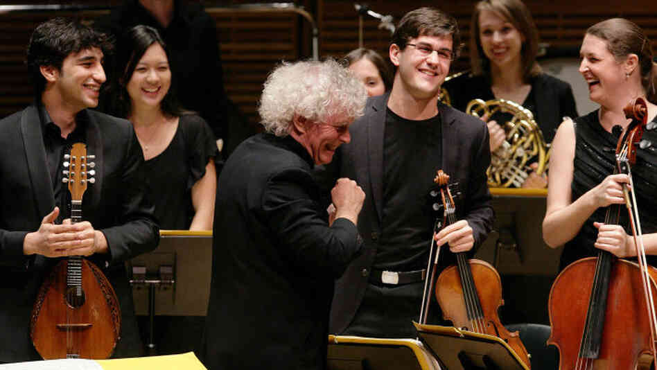 The Ensemble ACJW, conducted by Sir Simon Rattle (center), features musicians from the Academy, sponsored by Carnegie Hall and the Juilliard School. The violist to the right of Rattle is Nathan Schram.
