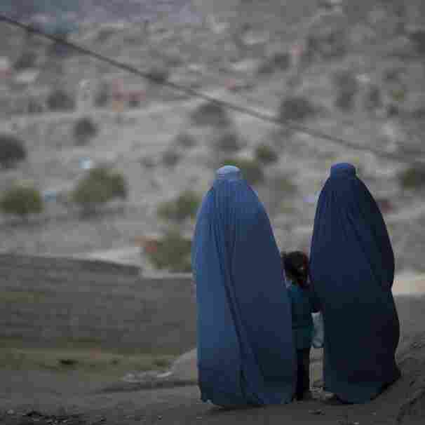 A girl stands among Afghan women clad in burqas  in Kabul last October.