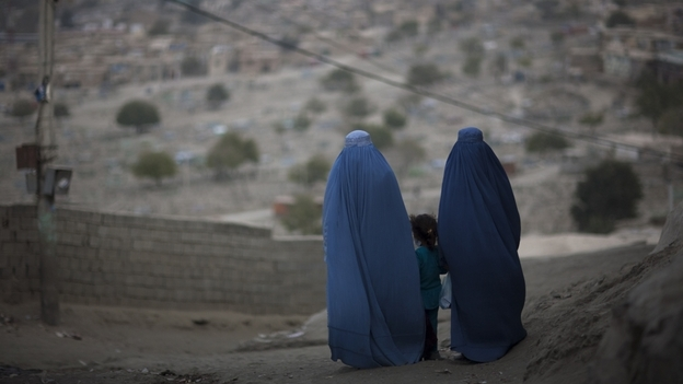A girl stands among Afghan women clad in burqas  in Kabul last October. (AP)