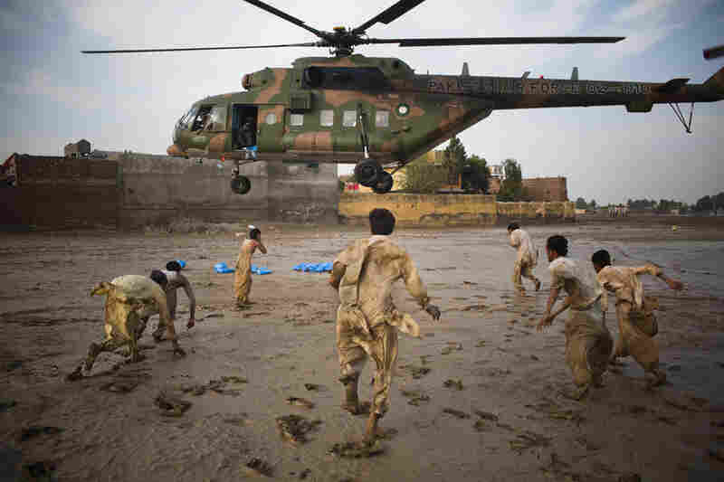 Flood victims scramble to recover water bottles dropped from a Pakistan Air force helicopter on August 2, 2010 in Nowshera, Pakistan.