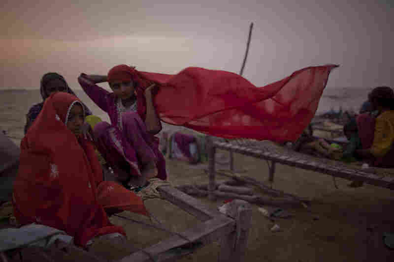 Young girls, whose families were displaced by floods, sit on a makeshift bed, as they take shelter on higher ground of a bund on August 29, 2010 in Thatta, near Hyderabad  in Sindh province, Pakistan.