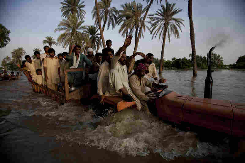 Villagers displaced from their homes by flooding travel through flood waters on the back of a tractor on August 11, 2010 on the outskirts of Muzaffargarh in Punjab, Pakistan.
