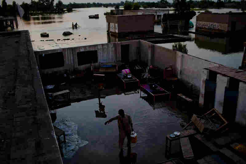 A boy walks through a flooded yard carrying water prior to Maghrib prayer and Iftar or breaking fast as it is called during the month of Ramadan on August 21, 2010 in the village of Vasandawali south of Muzaffargarh in Punjab, Pakistan.