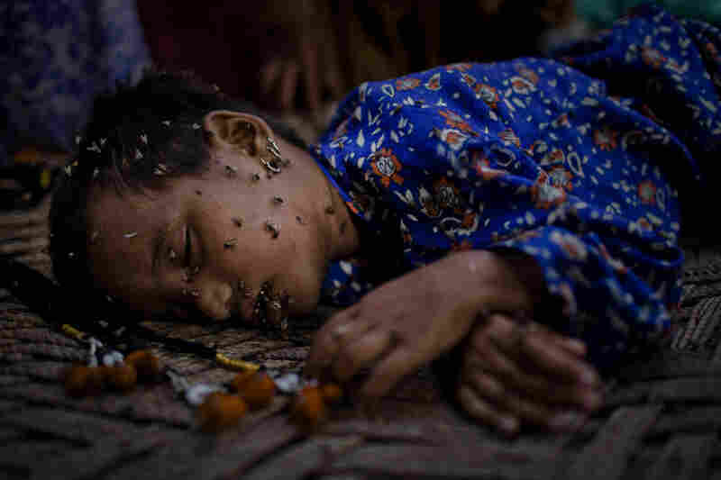 A young Pakistani girl, displaced by floods, and stranded on land only accessible by air, sleeps covered in flies, on a makeshift bed on August 27, 2010 in Garhi Khairo near Jacobabad in Sindh province, Pakistan.