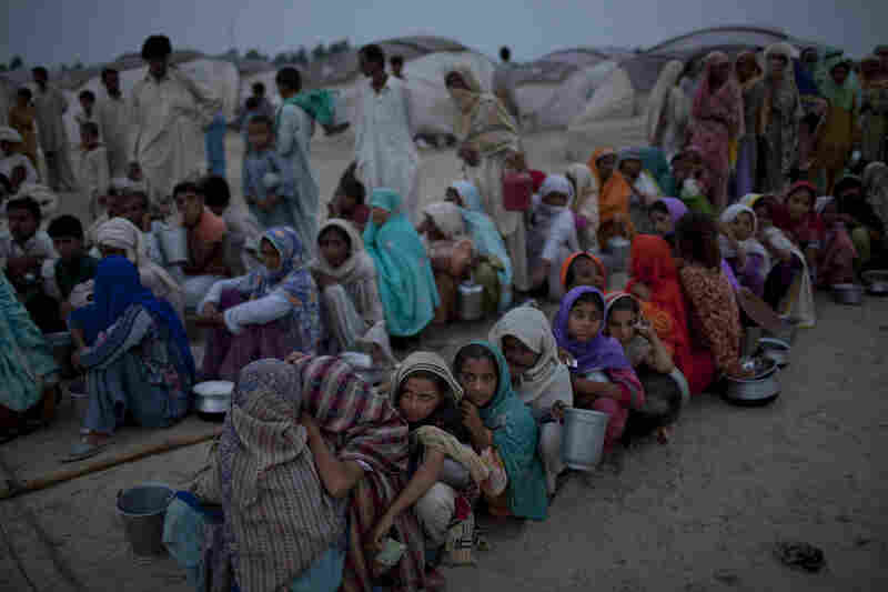 Villagers, displaced from their homes by flooding, hold empty containers as they queue for soup and relief rations on August 25, 2010 in the Sultan Colony Army flood relief camp near Muzaffargarh in Punjab, Pakistan.