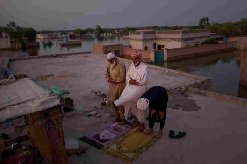 Pakistani villagers perform the Maghrib prayer, as they seek refuge on top of the roof of a Madrasa surrounded by flood waters, after Iftar or breaking fast in the month of Ramadan, on August 21, 2010 in the village of Vasandawali south of Muzaffargarh in Punjab, Pakistan.