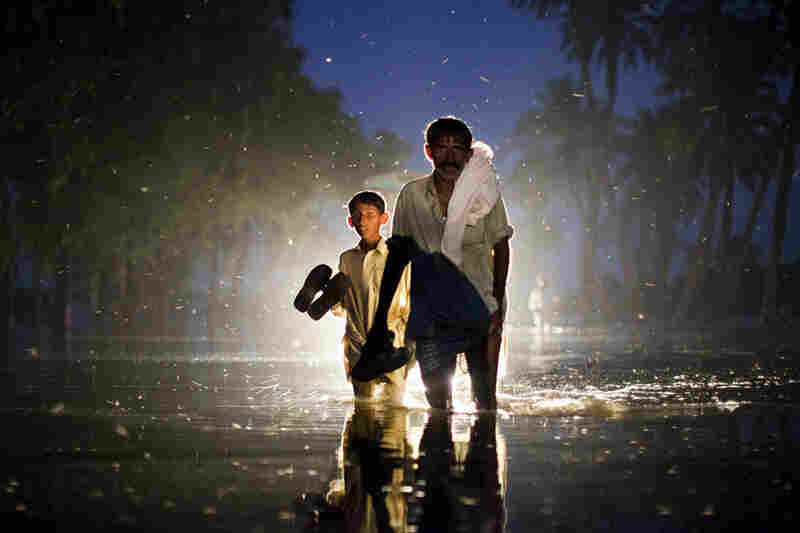 A Pakistani man and boy,  displaced by floods, walk through flood waters on August 22, 2010 in the village of Baseera near Muzaffargarh in Punjab, Pakistan.