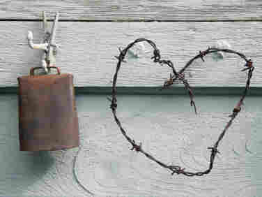 A cowbell and a barbed wire heart on a wall.