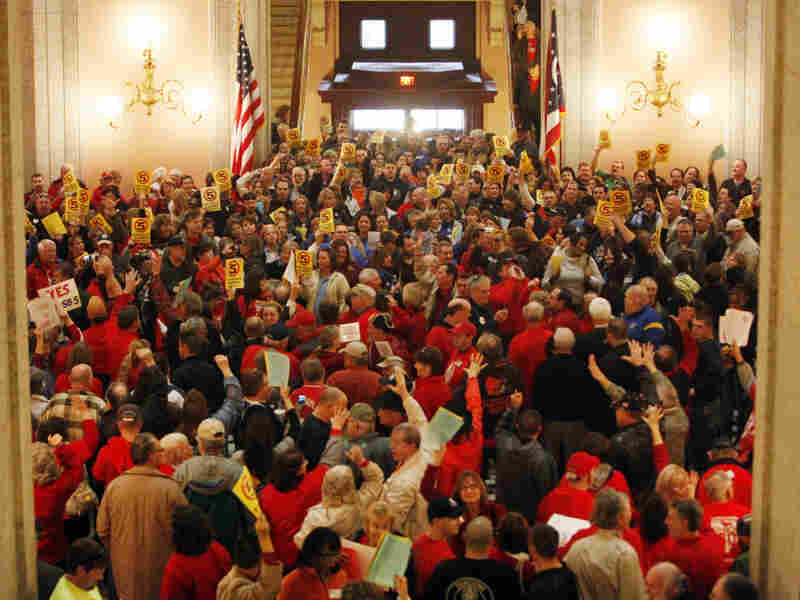Hundreds of supporters for and against a bill that would restrict collective bargaining rights of public employees fill the Ohio Statehouse rotunda on Thursday in Columbus.