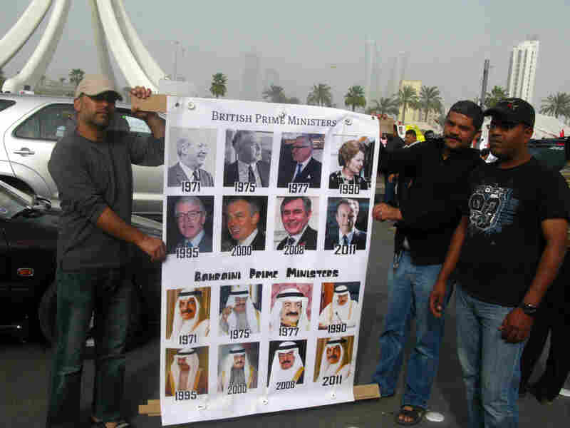 Men hold a sign comparing all British prime ministers since 1971 — eight of them — and Bahrain's prime minister during the same period, Sheik Khalifa bin Salman, in power for four decades. Demonstrators want, among other things, an  elected and term-limited prime minister as part of a constitutional  monarchy.