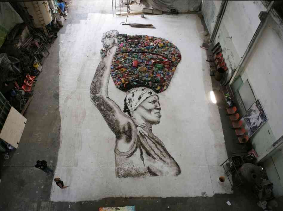 A massive portrait of Irma, resident chef at the Rio de Janiero landfill Jardim Gramacho, pieced together with scraps from the dump.