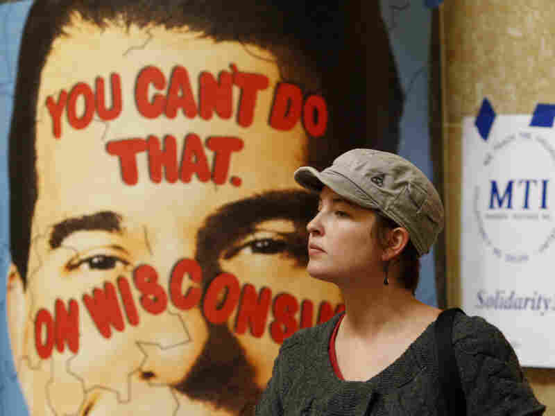 A protester looks on near a poster of Republican Gov. Scott Walker inside the state Capitol on Monday in Madison, Wis. Opponents to Gov. Walker's bill to eliminate collective bargaining rights for many state workers are taking part in their seventh day of protesting.