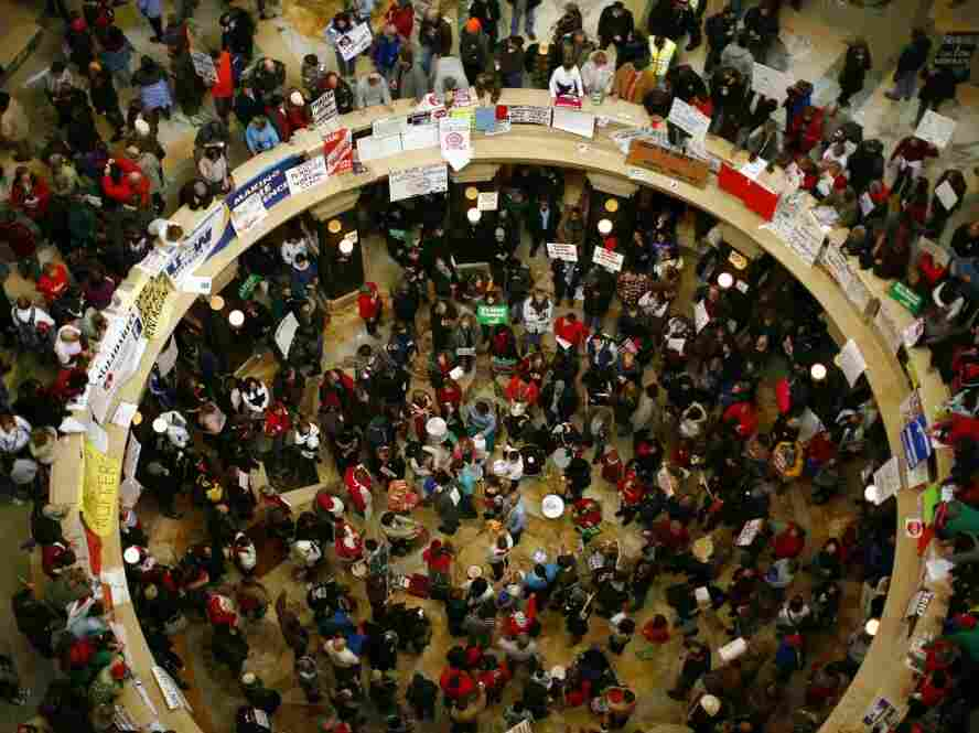 Demonstrators protest inside the Wisconsin state Capitol on Tuesday. With Senate Democrats still in hiding over the legislation proposed by the governor to restrict collective bargaining for public workers, Republicans threatened to move on without them in conducting other state business.