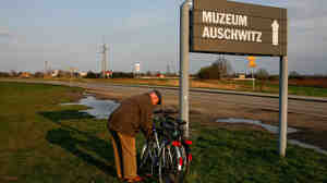 An elderly man from Oswiecim locks his bike to a sign at Auschwitz II-Birkenau that directs visitors