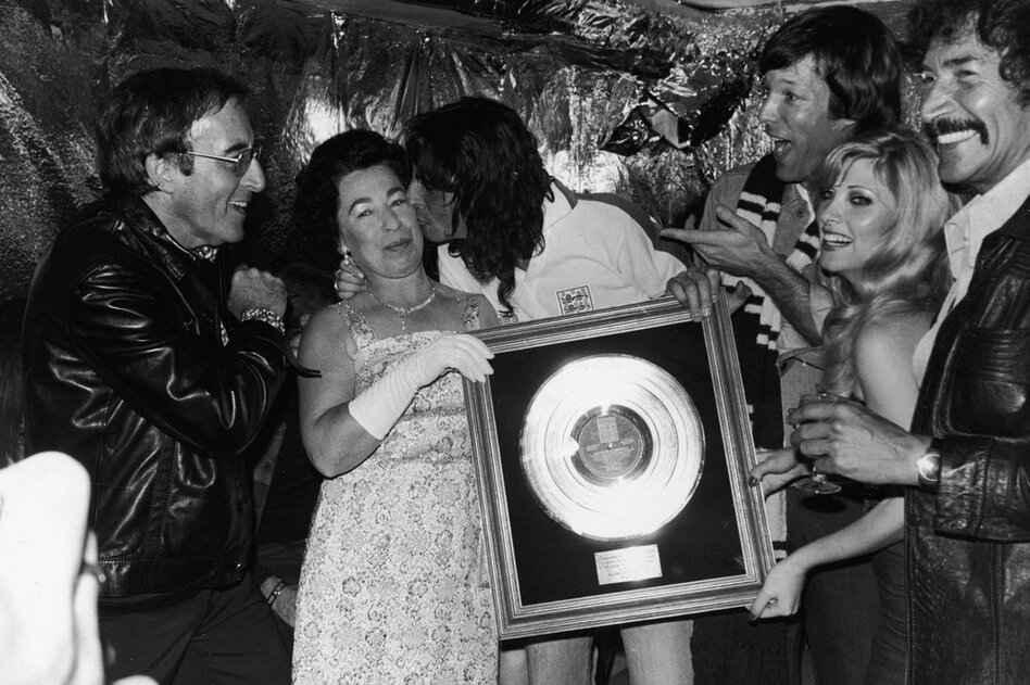 Although struggling with alcohol addiction through the rest of the '70s and early 1980s, Cooper continued to release hit albums and groundbreaking music videos. But after being rehospitalized in 1983 for alcoholism, he sobered up and released four more albums by the end of the '80s. Here, Cooper kisses a Queen Elizabeth II impersonator while holding his gold record plaque, in 1975.  (Getty Images)