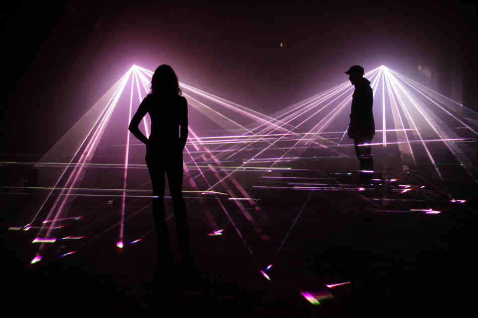 Artists pose in a laser projection entitled 'Speed of Light' at the Bargehouse on March 30, 2010 in London, England.