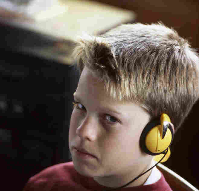 Boy sitting in chair, listening to music on headset