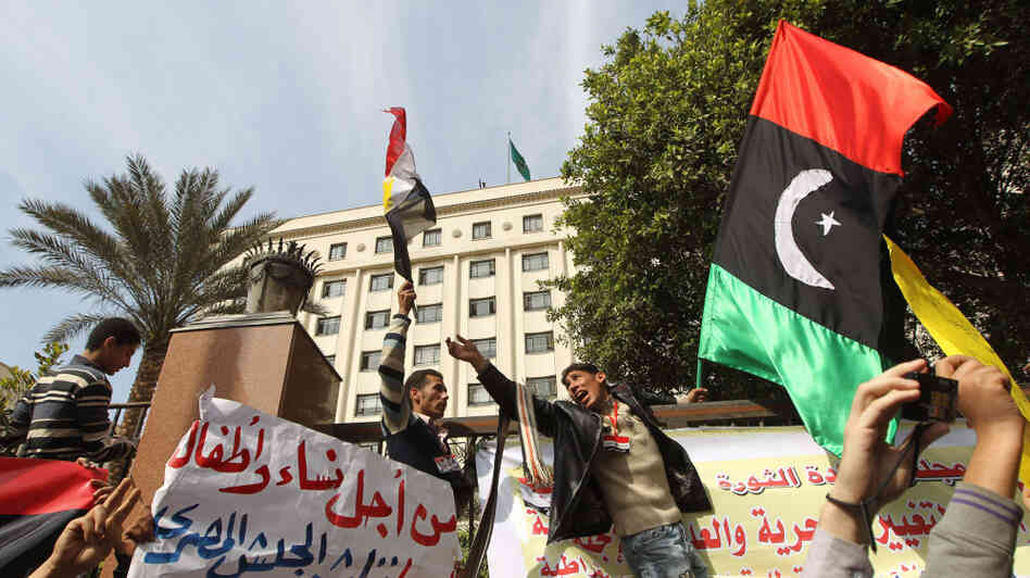 Protesters shout slogans against Libyan leader Moammar Gadhafi as they hold up the old Libya flag during a demonstration Tuesday outside the Arab League headquarters in Cairo.