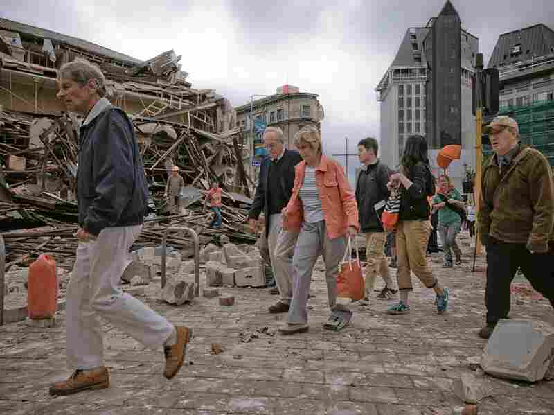 People walk through debris Tuesday. The region is still recovering from a 7.1 quake in September.