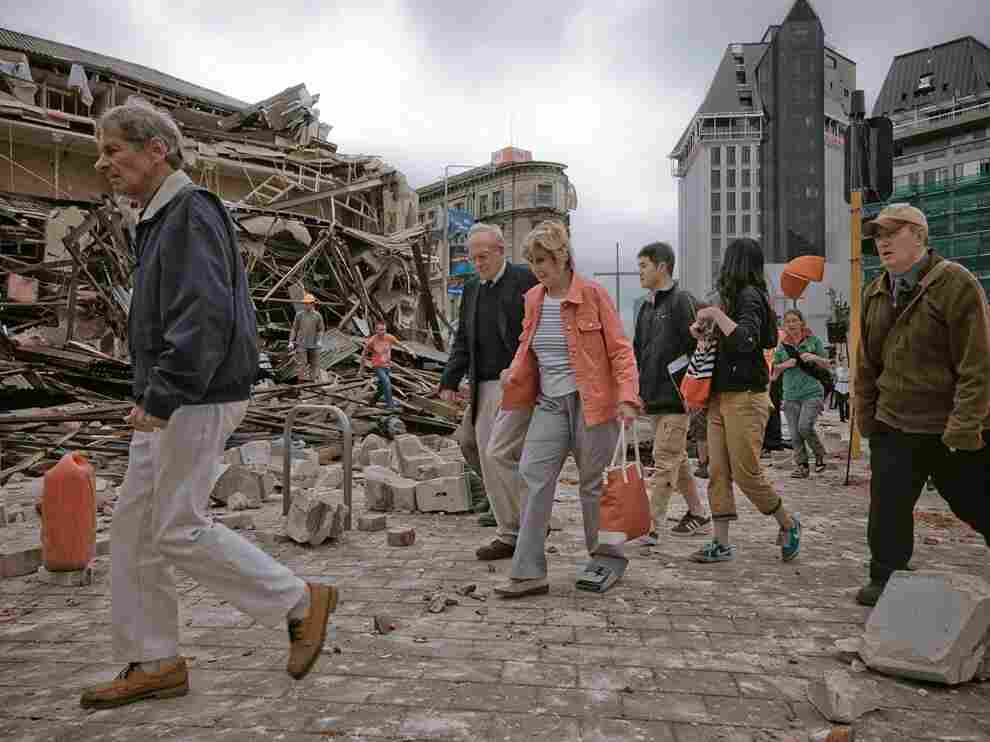 People walk through debris in the aftermath of a strong earthquake in Christchurch, New Zealand, Tuesday. The region is still recovering from a 7.1 quake in September.