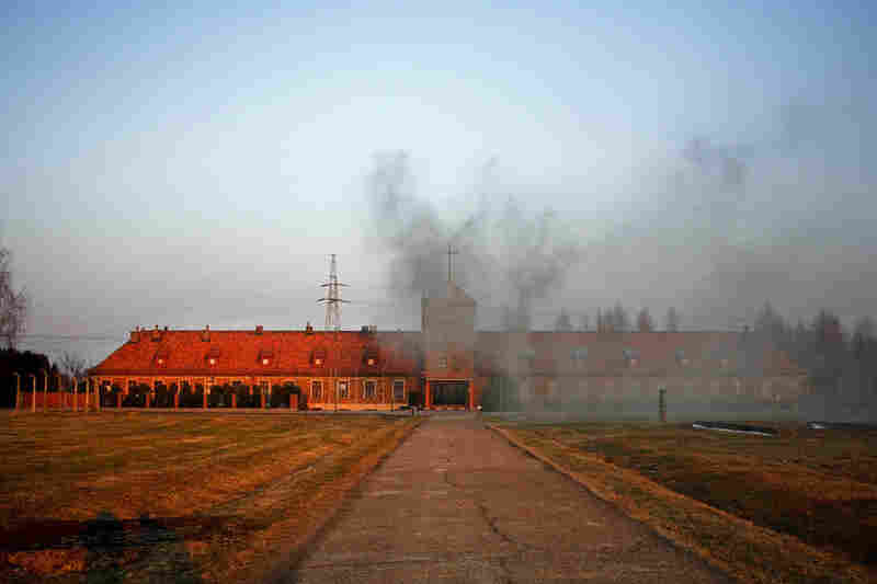 "Coal smoke billows from the former main entrance to extermination camp Auschwitz II-Birkenau, which is now an active Catholic Church for the village of Brzezinkau (""Birkenau"" in German)."
