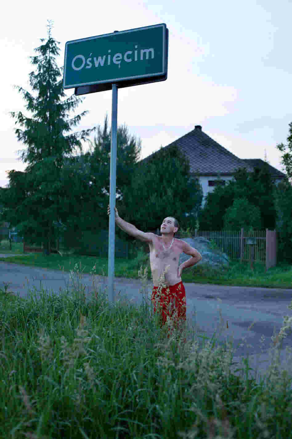 A man from a village bordering Oswiecim leans on a city limits sign for a portrait.