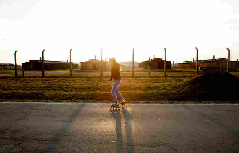 "A girl skates along from the adjacent village of Brzezinka to the town of Oswiecim (""Auschwitz"" in German). The road separates farmland and houses circling the camp museum."